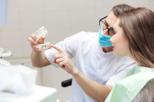 Man dentist show dentures teeth at dental surgery to his patient